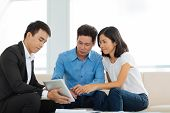 picture of family planning  - Real estate agent showing couple a house plan on the digital tablet - JPG