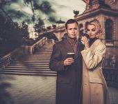 image of hot couple  - Elegant couple outdoors with cups of hot drink - JPG