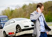 foto of tow-truck  - Man calling while tow truck picking up his broken car  - JPG