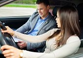 stock photo of seatbelt  - Driving instructor and woman student in examination car - JPG