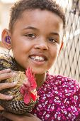 stock photo of rooster  - Cute African girl with hearing aid holding a rooster - JPG