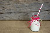 picture of milk glass  - White milk with polka dot straw in a glass retro milk bottle on burlap - JPG