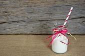 image of milk  - White milk with polka dot straw in a glass retro milk bottle on burlap - JPG