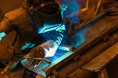 picture of protective eyewear  - Young man with protective mask welding in a factory
