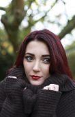 image of huddle  - A beautiful woman huddling in her jumper trying to keep warm - JPG