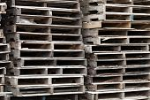 picture of wooden pallet  - Piles of wooden pallets ready for breaking up and recycling into firewood kindling or DIY projects - JPG