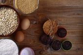 picture of sweetie  - Ingredients and baked sweeties such as brown cane sugar oatmeal flour eggs oatcakes and chocolate cupcakes on wooden table top horizontal photo - JPG