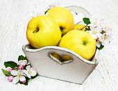 stock photo of apple blossom  - box with apples and apple tree blossoms on a wooden table - JPG