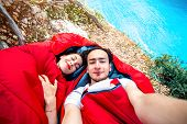stock photo of sleeping bag  - Young couple lying in red sleeping bags near the sea - JPG