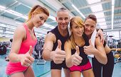 picture of cheer-up  - Group of friends with thumbs up smiling on a fitness center after hard training day. Selective focus on hands.