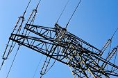 stock photo of transmission lines  - the poles of a power line against a blue sky - JPG