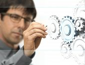 stock photo of mechanical engineer  - Caucasian engineer drawing gears on a transparent wall - JPG