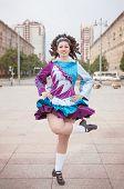 foto of wig  - Young woman in irish dance dress and wig dancing outdoor - JPG