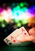 picture of poker hand  - Powerful poker hand with two aces in casino with colorful blured background - JPG