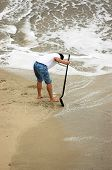 image of clam digging  - man on the beach looking for clams - JPG