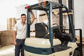 stock photo of forklift  - Manual worker leaning against the forklift in warehouse - JPG