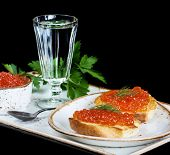 image of vodka  - Sandwiches with red caviar and glass of vodka on a porcelain plate isolated at black - JPG