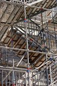pic of scaffold  - Construction scaffold on the a brown wall in the sunlight - JPG