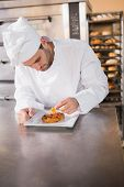 pic of pastry chef  - Focused baker putting flower on the pastry in the kitchen of the bakery - JPG
