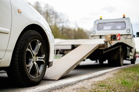 stock photo of towing  - Loading broken car on a tow truck on a roadside  - JPG
