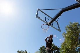foto of slam  - Young basketball player driving to the hoop for a high flying slam dunk - JPG