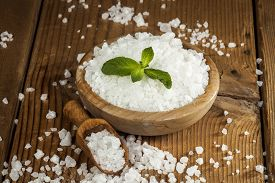 picture of crystal salt  - Sea salt in bowl and spoon on a wooden background - JPG