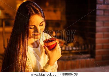 Woman Drinking Hot Coffee Relaxing At Fireplace.