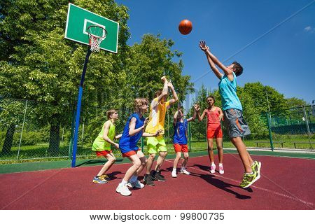Teenagers playing basketball game together