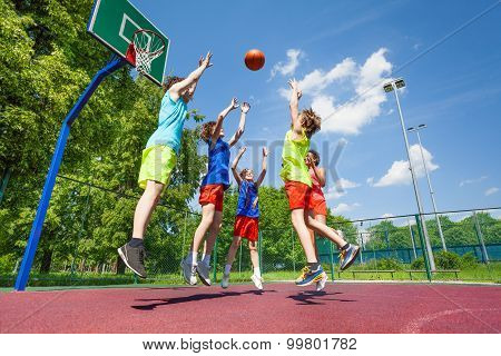 Children jump for flying ball during basketball