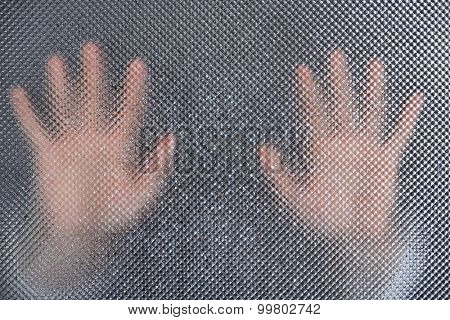 Male hands behind  wet glass, close-up
