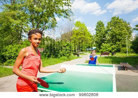 Two girls playing ping pong outside during summer
