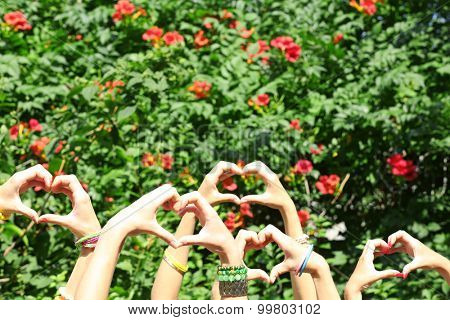 Young people makes hearts using fingers outdoors