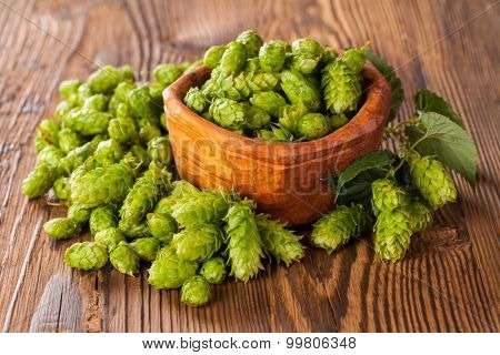 Fresh green hops on a wooden desk, served in bowl