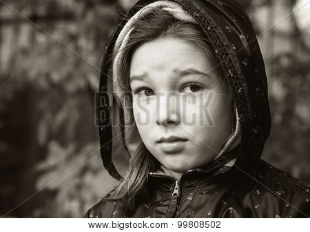 Outdoor portrait of a little girl in autumn jacket with a hood. Black and white photo