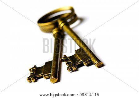 Old keys laying on top of white background isolated golden ancient antique symbol of security and safety