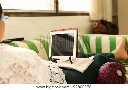 Elderly Woman On The Couch With Laptop
