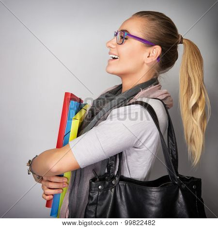 Side view of nice blond student girl wearing glasses and laughing in the studio, holding in hands folders and bag isolated on gray background