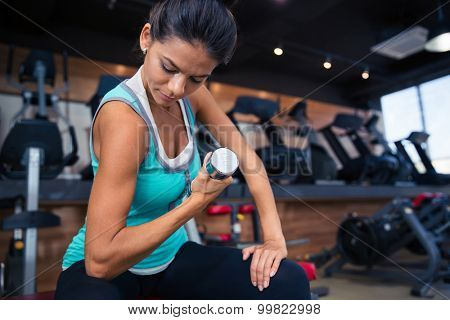 Young girl workout with dumbbell on the bench in gym