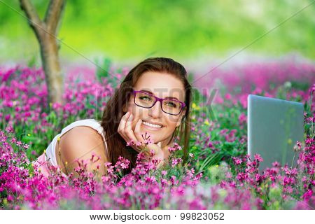 Portrait of beautiful smiling student girl lying down on flowers meadow in the university garden, with pleasure working on laptop outdoors, using wireless internet