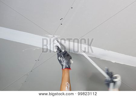 Plasterer Spreading Plaster To Ceiling