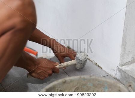Man Laying Tile With Rubber Hammer