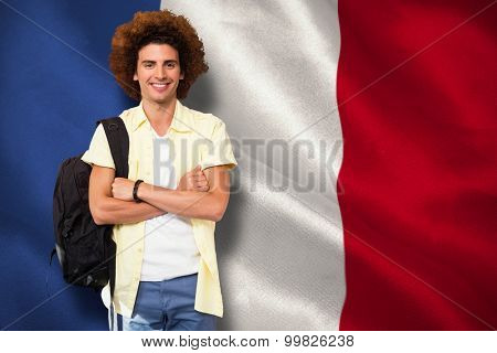 Young man with arms crossed in office corridor against digitally generated france national flag