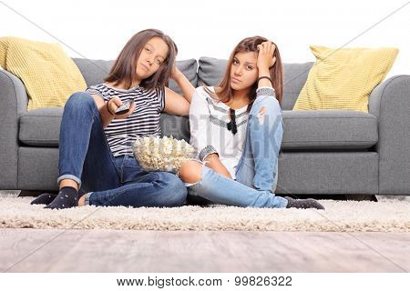 Two bored teenage girls watching TV and changing the channels isolated on white background