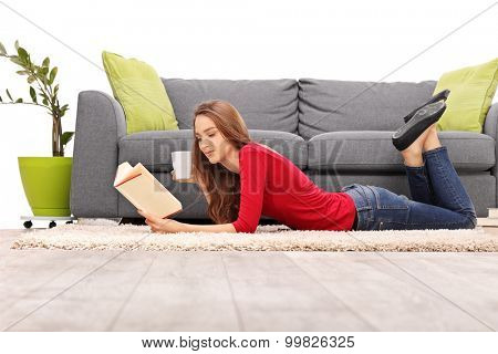 Young brunette woman lying on the floor and reading a book in front of a gray sofa isolated on white background