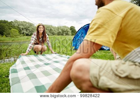 camping, travel, tourism, hike and people concept - happy couple laying picnic blanket at campsite