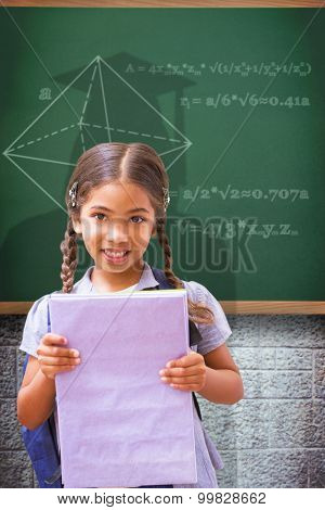 Cute pupil smiling at camera holding notepad against green