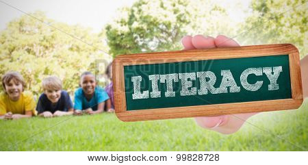 The word literacy and hand showing chalkboard against happy friends in the park