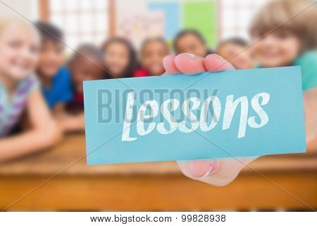 The word lessons and hand showing card against cute pupils smiling at camera in classroom