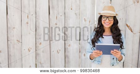 Pretty hipster smiling at camera holding tablet against bleached wooden fence