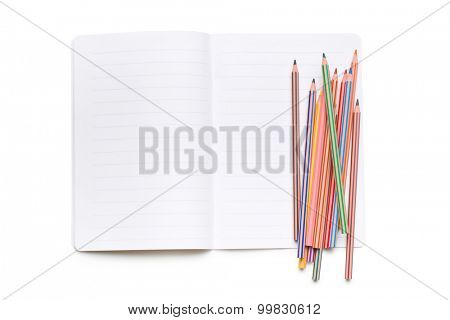 colored pencils and open workbook on white background